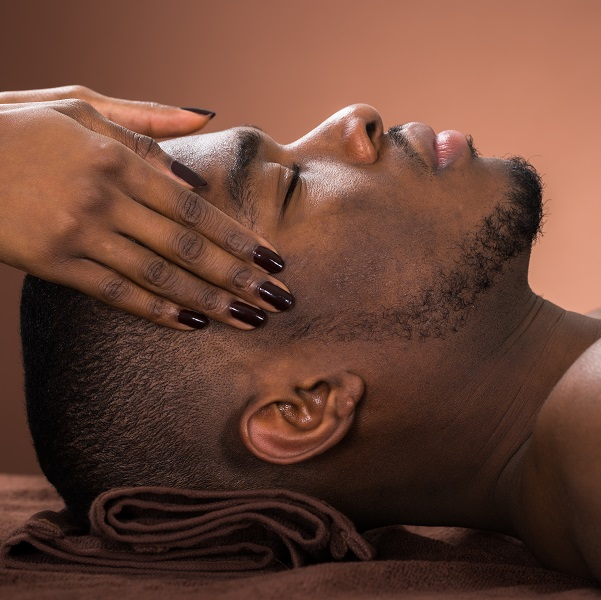 Young,African,Man,Receiving,Forehead,Massage,In,Spa